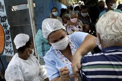 Una trabajadora de salud vacuna a un adulto mayor en Brasil (Reuters/ Ricardo Moraes)
