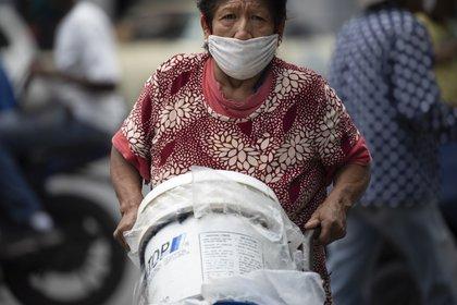 Una mujer, con mascarilla para protegerse del coronavirus, empuja un carrito con recipientes llenos de agua, en Caracas, Venezuela, el 20 de junio de 2020. Se estima que el 86% de los venezolanos reportó problemas con el suministro de agua, incluyendo un 11% que no tiene, según una encuesta realizada por la ONG Observatorio Venezolano de Servicios Públicos entre 4.500 residentes en abril. (AP Foto/Ariana Cubillos)
