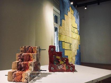 Esculturas que representan cómo se comrpime la ropa usada para ser donada a los países periféricos. Detrás una chakana de grandes dimensiones