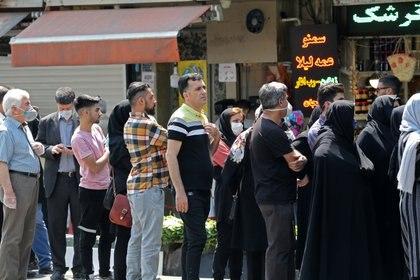 Ciudadanos iraníes sin observar el distanciamiento social hacen cola frente a una oficina de cambio en la capital Teherán el 9 de mayo de 2020 (Foto de ATTA KENARE / AFP)