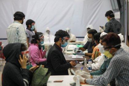 Los ciudadanos indios, que quedaron varados en Singapur debido al brote de la enfermedad coronavirus (COVID-19), son examinados por médicos en el aeropuerto a su llegada a Nueva Delhi, India, el 8 de mayo de 2020. (REUTERS/Anushree Fadnavis)