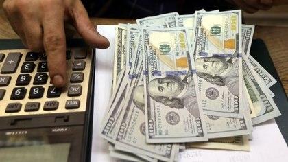 Imagen de archivo de un empleado contando dólares en una casa de cambio en el centro de El Cairo, Egipto. 20 marzo 2019. REUTERS/Mohamed Abd El Ghany.