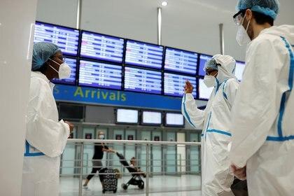 Trabajadores de la salud esperan a los pasajeros para hacerles la prueba de COVID-19 a su llegada al aeropuerto Charles de Gaulle, cerca de París, Francia, el 31 de julio de 2020 (REUTERS/Christian Hartmann)