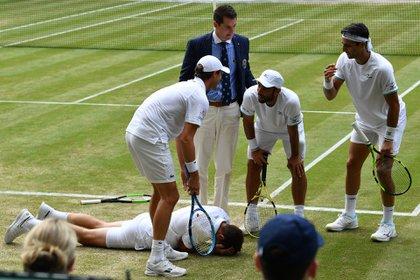 El francésNicolas Mahutquedó tendido en el suelo tras recibir un pelotazo del colombiano Robert Farahen la final de dobles masculino deWimbledon (AFP)