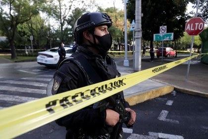 Un oficial de policía detrás de una cinta que acordona el área donde tuvo lugar el atentado contra García Harfuch (Foto:REUTERS/Henry Romero)