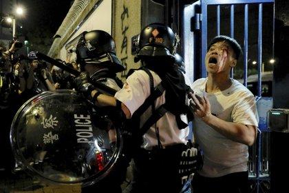 Un manifestante pide ayuda mientras es reprimido por la policía. (AP Photo/Vincent Yu)