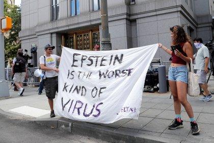 """Julio 2020. En las audiencias contra Maxwell en Nueva York la gente se presentó para expresar su repudio. """"Epstein es el peor tipo de virus"""", dice la bandera. Foto: Reuters."""
