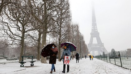 People walk with umbrellas in Champ de Mars park on January 16, 2021 after a snowfall in Paris, as the Eiffel Tower is seen in the background. - 32 departments, including Paris and the entire Ile-de-France, are placed on snow-ice alert by Meteo-France. (Photo by Ludovic MARIN / AFP)