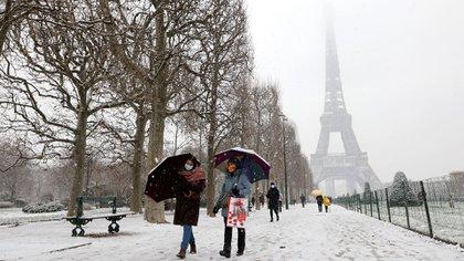 La gente camina con paraguas en el parque Champ de Mars el 16 de enero de 2021 con la Torre Eiffel de fondo (Foto de Ludovic MARIN / AFP)