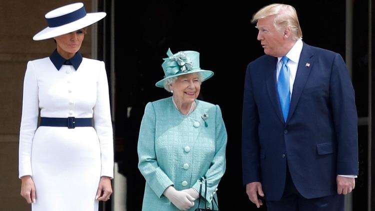 La reina Isabel II de Inglaterra, rodeada por el presidente estadounidense Donald Trump (a su izquierda) y su esposa Melania Trump (a su derecha) (AFP)