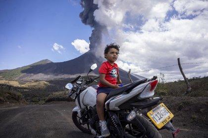 Un niño, sentado sobre una motocicleta durante una erupción del volcán Pacaya, de fondo, visto desde San Vicente Pacaya, Guatemala, el 3 de marzo de 2021. (AP Foto/Santiago Billy )