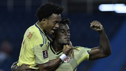 Colombia's Duvan Zapata (R) celebrates with teammate Juan Guillermo Cuadrado after scoring against Venezuela during their 2022 FIFA World Cup South American qualifier football match at the Roberto Melendez Metropolitan Stadium in Barranquilla, Colombia, on October 9, 2020, amid the COVID-19 novel coronavirus pandemic. (Photo by Gabriel Aponte / POOL / AFP)