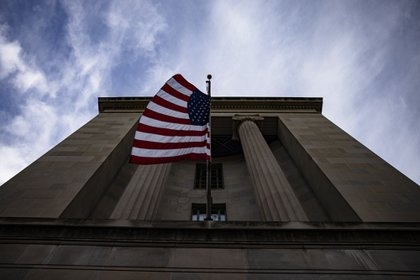 An American flag flies outside the U.S. Department of Justice (DOJ) headquarters in Washington, D.C., U.S., on Saturday, Jan. 2, 2021. A group of 11 Republican senators is pledging to oppose certification of President Donald Trumps election loss, rejecting leadership who warned against attempts to undermine the election or risk splintering the party.