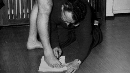 Adolf Dassler tomando medidas para la fabricación, al inicio casi artesanal, de sus calzados deportivos