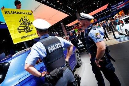 Oficiales de policía observan cómo un activista de Greenpeace se subió a un coche expuesto como señal de protesta contra el calentamiento global