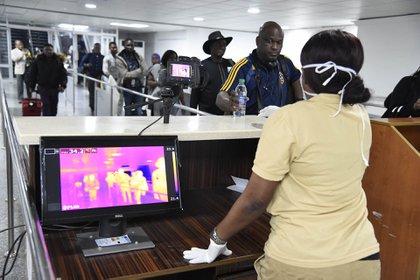 A los pacientes que llegan al aeropuerto de Nigeria se les toma la temperatura (Photo by PIUS UTOMI EKPEI / AFP)