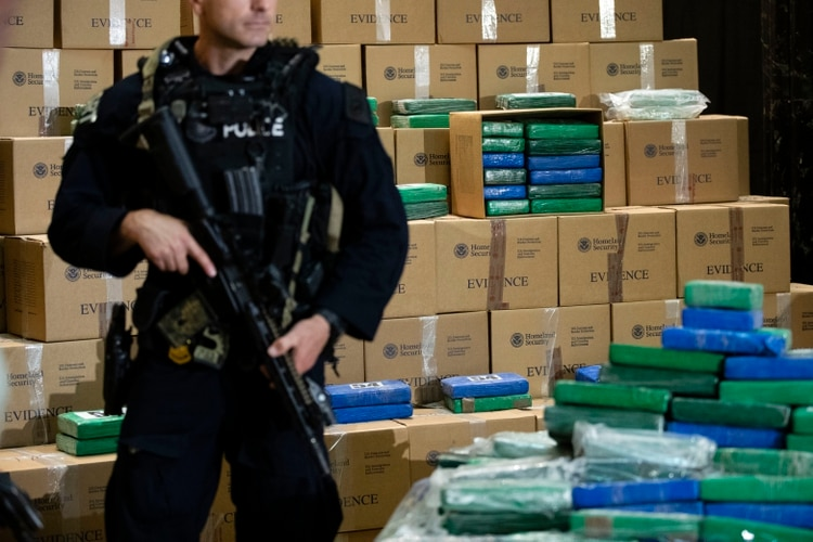 Un agente de policía monta guardia sobre parte del alijo de cocaína incautado de un buque en Filadelfia (AP Foto/Matt Rourke)