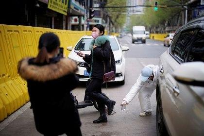 Un conductor con un traje protector desinfecta a una mujer en una calle de Wuhan, provincia de Hubei, el epicentro del brote de la enfermedad coronavirus de China (COVID-19), el 3 de abril de 2020. REUTERS/Aly Song