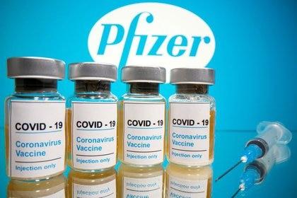 """FOTO DE ARCHIVO: Frascos con la pegatina de """"COVID-19 / Vacuna contra el Coronavirus / Sólo inyección"""" frente al logo de Pfizer en esta ilustración tomada el 31 de octubre de 2020. REUTERS/Dado Ruvic/Ilustración"""