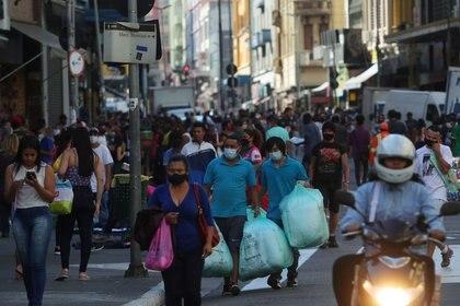 Personas caminan con bolsas en una popular calle comercial en medio del brote de COVID-19 en Sao Paulo, Brasil. 19 de junio de 2020. REUTERS/Amanda Perobelli