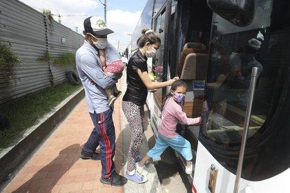 En esta imagen del 30 de abril de 2020, migrantes venezolanos suben a un autobús con destino a la frontera venezolana, en medio de la pandemia del nuevo coronavirus, en Bogotá, Colombia. (AP Foto/Fernando Vergara)