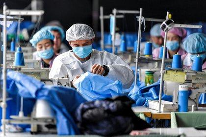 Trabajadores fabrican trajes de protección en una fábrica de equipos médicos en Urumqi, Región Autónoma Uigur de Xinjiang, China. Foto tomada el 27 de enero de 2020 (REUTERS)
