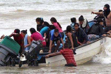 Migrantes venezolanos, recientemente deportados, llegan a la costa de la playa de Los Iros tras su regreso a Trinidad y Tabago, el 24 de noviembre de 2020 (Lincoln Holder/Cortesía Newsday/Handout vía REUTERS)