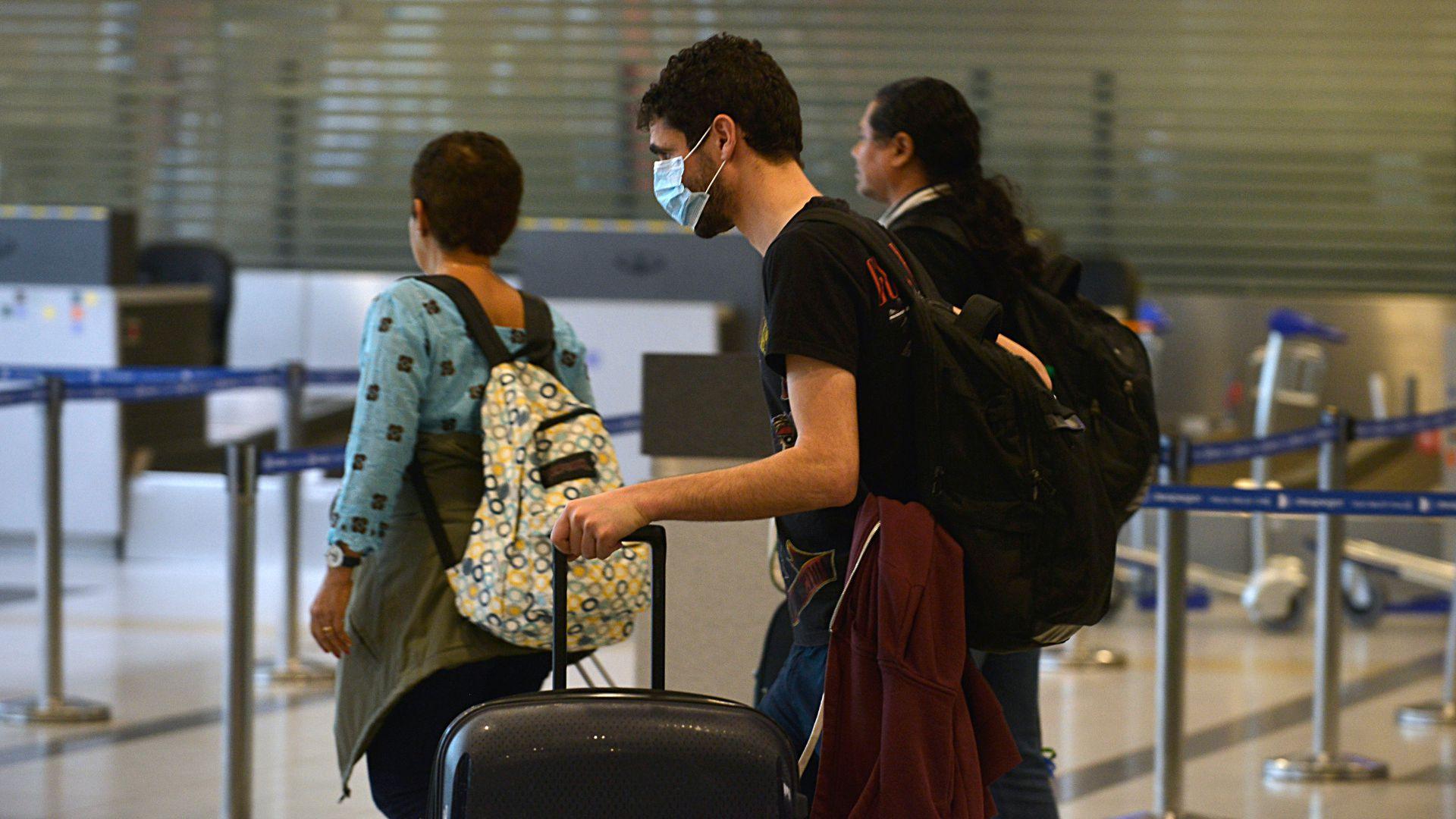 Pasajeros con barbijos en el aeropuerto de Ezeiza (Gustavo Gavotti)