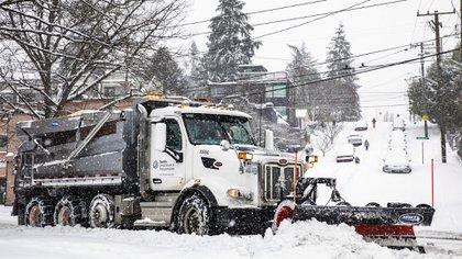 Un camión trata de despejar la nieve en una calle de Seattle, en el oeste del país.