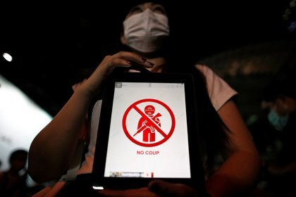 A person holds up a tablet as Myanmar citizens living in Thailand protest against the military coup outside Myanmar embassy in Bangkok, Thailand February 4, 2021. REUTERS/Jorge Silva
