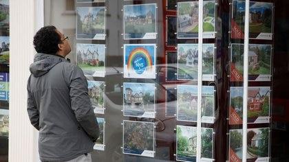 FOTO DE ARCHIVO: Un hombre frente al escaparate de una inmobiliaria en Hale, Reino Unido, el 13 de mayo de 2020. REUTERS/Phil Noble/Foto de archivo