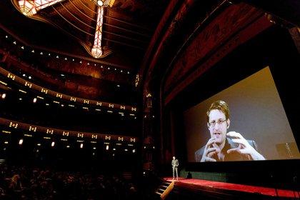"""Edward Snowden habla al público reunido en un teatro de Amsterdam en una teleconferencia desde Rusa para el estreno de la película """"Snowden"""" en 2016 (EFE/Sander Koning)"""
