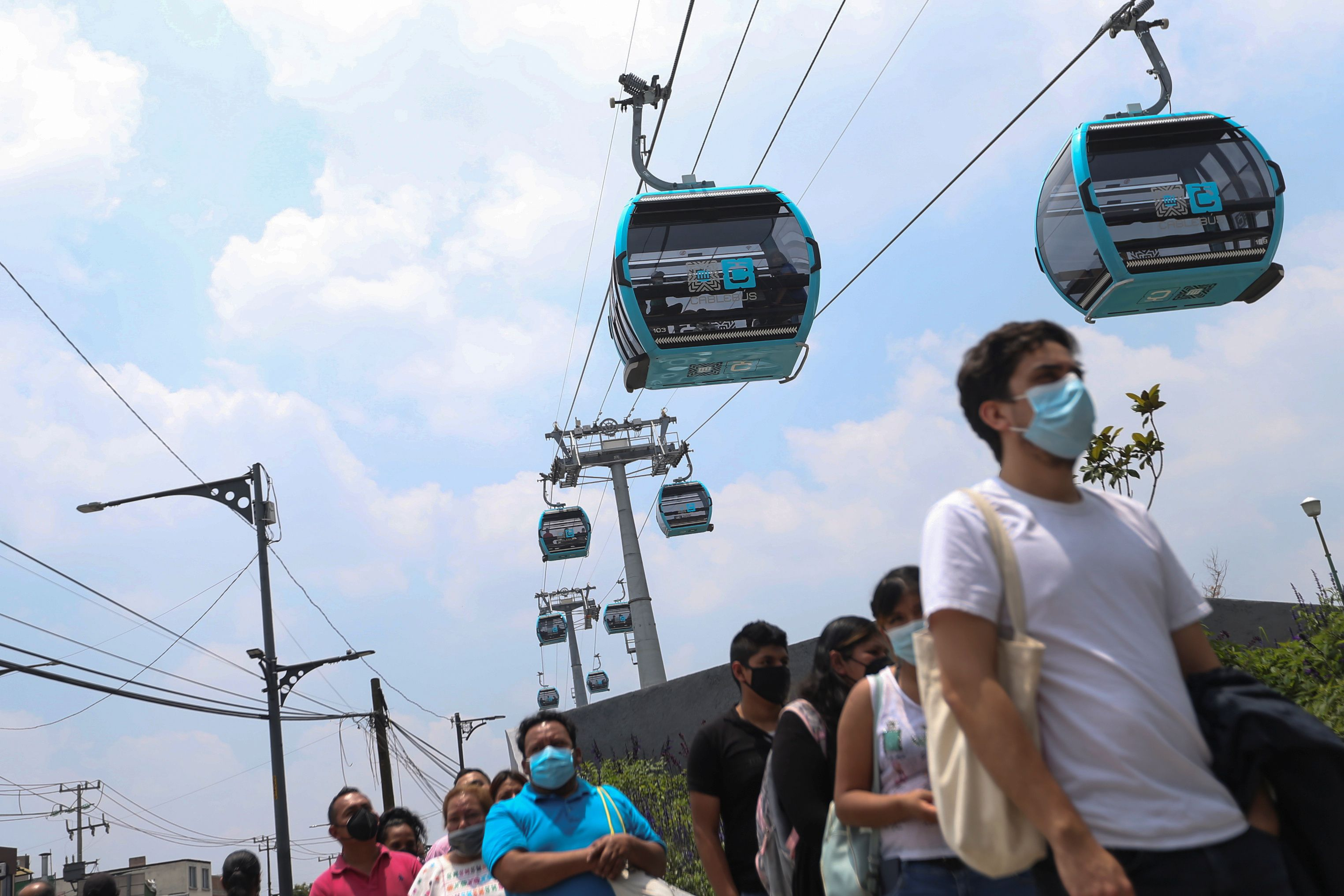 Passengers line up before traveling on a cable car system dubbed the Cablebus during the inauguration of a section in Mexico City, Mexico, July 11, 2021. REUTERS/Edgard Garrido