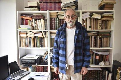 """En su escritorio repleto de libros, textos, un saxofón que intenta descifrar y un cartel que dice : """"abuelo te amo"""""""