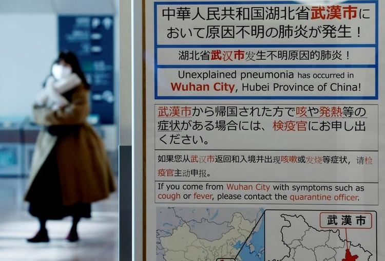 Una mujer con una mascarilla pasa cerca de un aviso de cuarentena puesto sobre la ciudad china de Wuhan por un nuevo virus. Enero 2020, REUTERS/Kim Kyung-Hoon