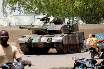Personas pasam frente a un tanque del ejército de Chad cerca del palacio presidencial en N'djamena, Chad, el 19 de abril de 2021. REUTERS / Fotógrafo autónomo