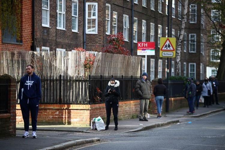 Gente siguiendo las reglas de distanciamiento social mientras hacen cola en la Oficina de Correos de Kennington, mientras continúa la propagación del coronavirus (COVID-19), Londres, Reino Unido, 4 de abril, 2020. REUTERS/Hannah McKay