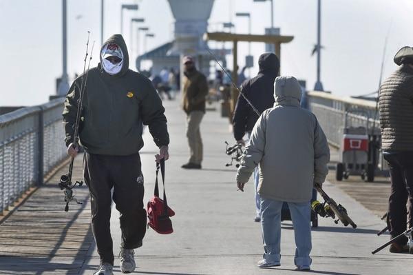Pescadores en Fort Walton (Florida), habituados al calor, se abrigan para continuar su jornada (AP)