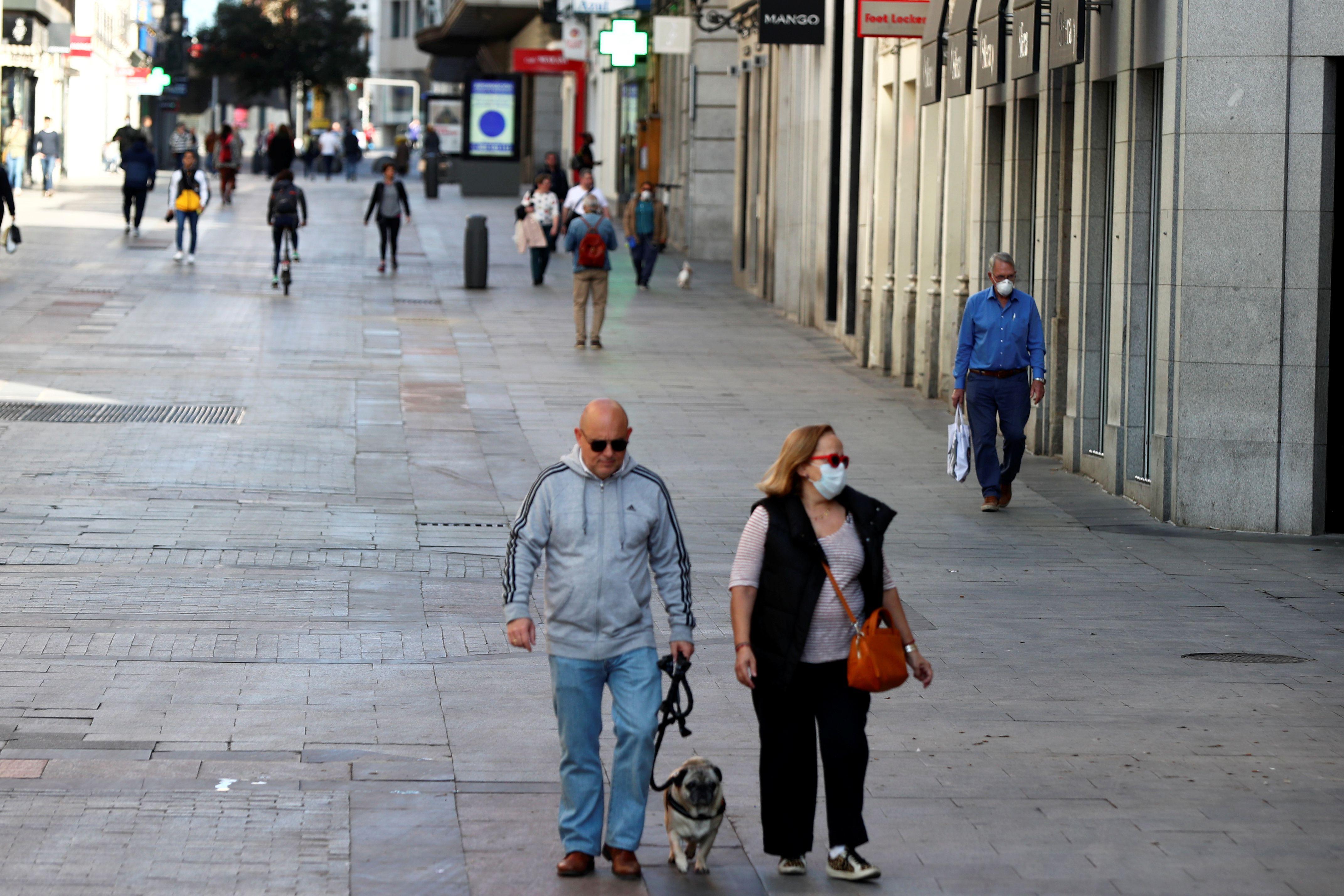 La gente, con máscaras protectoras, camina por una calle vacía debido al brote de coronavirus en el centro de Madrid, España, el 14 de marzo de 2020. REUTERS/Sergio Pérez