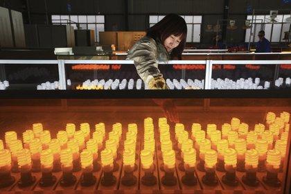 Photographie montrant une femme travaillant dans une usine d'ampoules à Suining, Chine.  EFE / ZHONG MIN / Archives