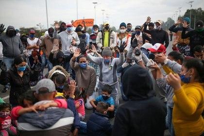 Inmigrantes venezolanos con mascarillas participan en una protesta por un bloqueo de buses que contrataron para llegar a la frontera con Venezuela en Bogotá. FOTO DE ARCHIVO. REUTERS/Luisa Gonzalez