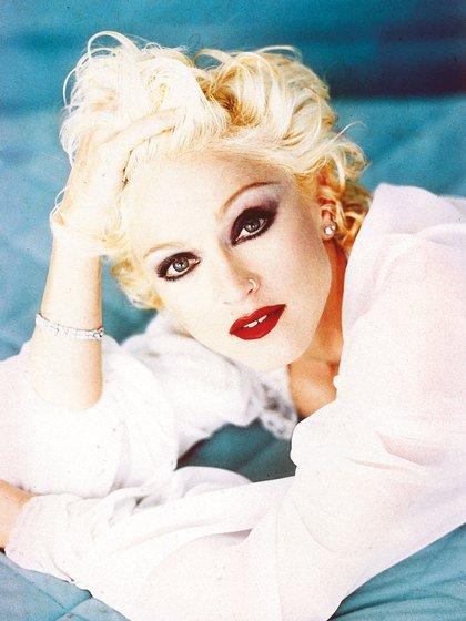 Madonna en los 90: Pelo corto platinado, piel blanca, ojos delineados, labios intensos y lunar