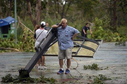 Turista habla por teléfono apoyado en un anuncio que fue derribado por fuertes vientos tras el paso del delta del huracán en Cancún, Quintana Roo Foto: (PEDRO PARDO / AFP)