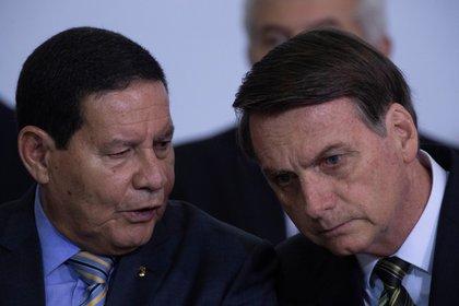 El vicepresidente de Brasil Hamilton Mourao (izquierda), habla con el presidente de Brasil, Jair Bolsonaro (EFE)