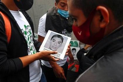 Un hombre sostiene una cerámica con la imagen de uno de los estudiantes desaparecidos, mientras la gente participa en una protesta frente a la Fiscalía General, antes del sexto aniversario de la desaparición de 43 estudiantes de la Escuela Normal Rural de  Ayotzinapa, en la Ciudad de México. México 25 de septiembre de 2020.