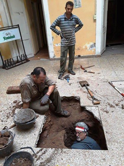 El arqueólogo Daniel Schavelzon asoma por un hueco. Debajo hallaron un tramo del Zanjón de Granados, un arroyo del tiempo de la Colonia.