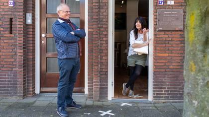 De pie en el pueblo neerlandés de Baarle-Nassau, Willem van Gool, funcionario de turismo local, conversa con Sylvia Reijbroek, cuya galería de arte se encuentra en el poblado belga de Baarle-Hertog, el 2 de mayo de 2020 (Ilvy Njiokiktjien/The New York Times).