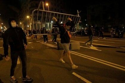 Un hombre avanza con una valla en Barcelona durante la manifestación por la libertad de Hásel este viernes por la noche (REUTERS/Albert Gea)