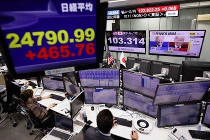 Un operador de mercados mira los monitores con el índice Nikkei y las noticias sobre las elecciones en EEUU en una correduría de Tokio, Japón. 9 noviembre 2020. REUTERS/Issei Kato