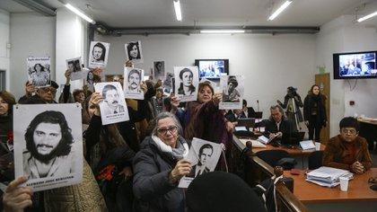 Los familiares de las víctimas cumplen con el ritual de cada audiencia: muestran las fotos de sus parientes apenas los represores se sientan en el banquillo